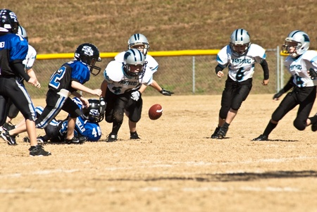 Cumming, GA, USA - November 8 : Group of young boys on the football field chasing a loose ball.  Forsyth County, Cumming, GA, November 8, 2008,  boys team of 8-9 year olds during a game, the Panthers and War Eagles.