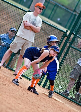 Cumming, GA, USA - April, 18 : A young girl on first base watching the action at home. Forsyth County, Cumming, GA April 18, 2009, a regular season game of the Lady Gators vs the Bennet Park Blues. Stock Photo - 8944913