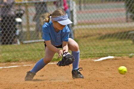 Young girl trying to catch a softball, lens zoom effect added.