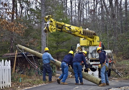 Tiger, GA, USA - March 4, 2011 - A group of men working to repair lines and poles damanged during a recent storm.
