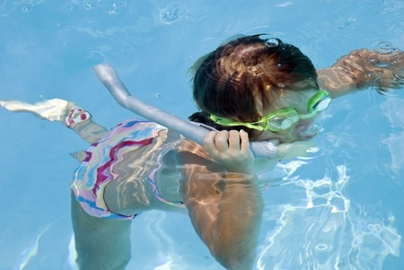 A young girl in a pool with a snorkle. photo