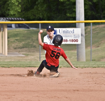 Forsyth County, Cumming GA - April 19, 2010-The baseman is concentrating on making the out as a young boy slides into third plate. A regular season game between the Bulldogs and the Raiders in recreation department program. Stock Photo - 9256680