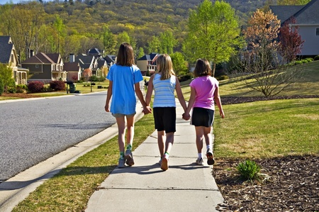 Three young girls going up a sidewalk in a neighborhood holding hands.