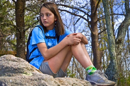 Young girl sitting taking a break on a hike. photo