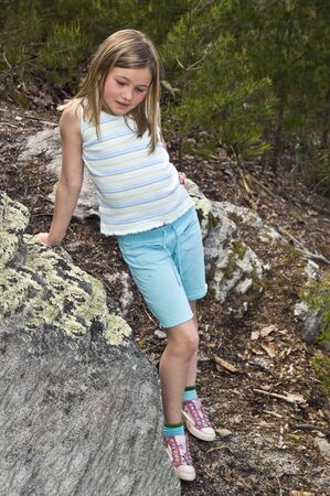 A young girl standing by some rocks looking down and thinking. photo