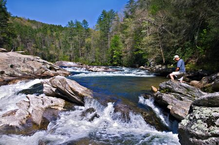 outdoorsman: Man standing on the rocks at the edge of a beautiful quickly flowing river.  This is an area of the Chatooga River called Bull Sluice when the water is low. Stock Photo