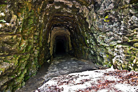 limestone caves: An old tunnel carved out of a rock mountain left abandoned. Stock Photo
