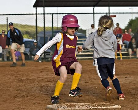 Cumming, GA, USA; April 16, 2011  - A young girl during a softball game in Forsyth County, Cumming GA, making her run to first base.  A regular season game between the Diamonds and the Warriors.