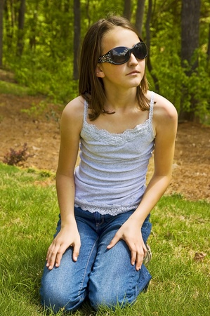 A cute young girl outside with stylish sunglasses, she has a thoughtful expression.