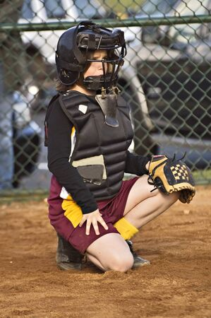 A young girl behind home plate watching intently ready to make a play. photo