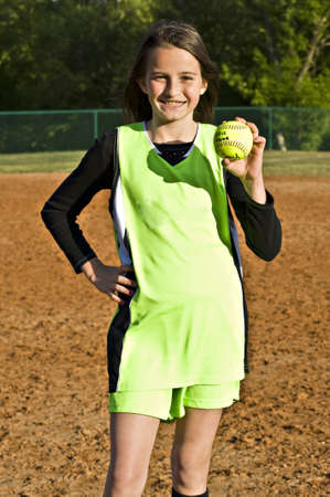 A young girl proudly showing the game ball she was awarded after a softball game.