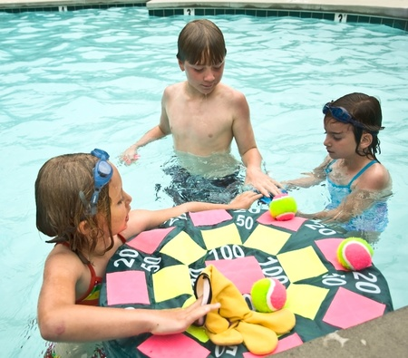 Three children getting ready to play a game in the swimming pool.