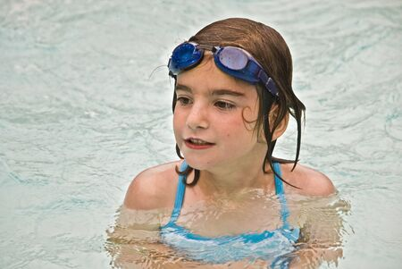 A young girl enjoying the swimming pool on a hot day at home, camp or vacation.  photo