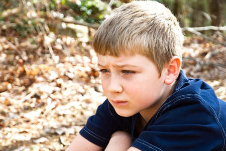 maybe: A young boy sitting outdoors, maybe hes thinking, not feeling well, or lost, the expression could relate to many emotions. Stock Photo
