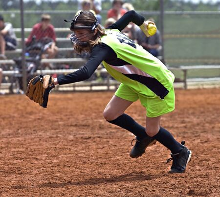 A young girl with ball in hand racing to make an out in a softball game. Stock Photo