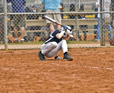 agachado: Un joven eludir al bate de la bola que viene a la cabeza.