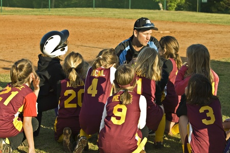 Cumming, GA, USA; April 16, 2011  - A coach talking to the girls on his team in Forsyth County, Cumming GA for a regular season game between the Diamonds and the Warriors. Stock Photo - 9397174