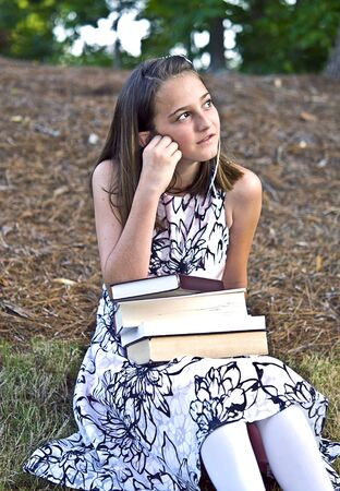 next year: A young girl sitting outdoors with books, thoughtful expression.  What will next year bring, she just graduated to middle school. Stock Photo