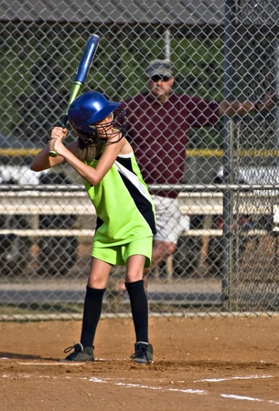 A preteen girl at bat with her coach watching.