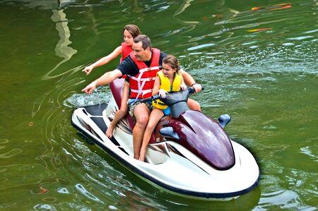 moto acuatica: Un hombre y sus hijos en una moto de agua apuntando a algo. Foto de archivo