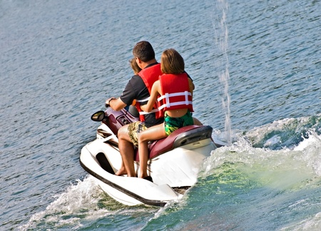 A man and his daughters going out on a jet ski. Stock Photo
