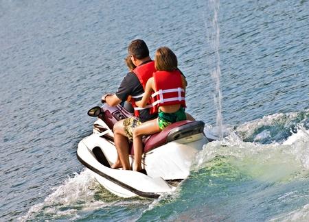 going out: Un uomo e le sue figlie andando fuori su un jet ski. Archivio Fotografico