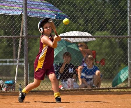 CUMMING, 조지아  미국 -5 월 21 일 : 미확인 된 어린 소녀 2010 년 5 월 21 일 Forsyth 카운티, Cumming 조지아에서 작은 리그 소프트볼 경기 도중 히트 만들기.