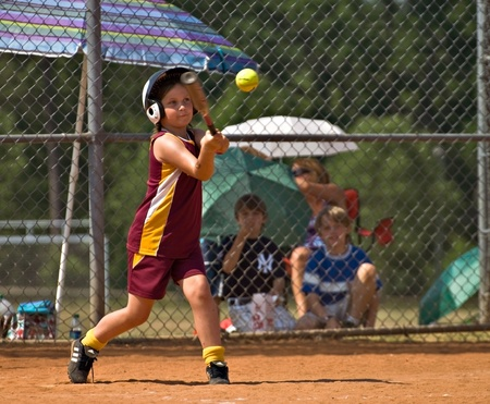 youth sports: CUMMING, GAUSA - MAY 21:  Unidentified young girl making a hit on May 21, 2010 in Forsyth County, Cumming GA, during a little league softball game.