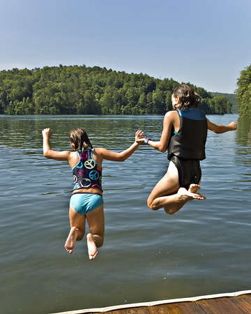 safe water: Two girls holding hands and jumping into a lake. Stock Photo