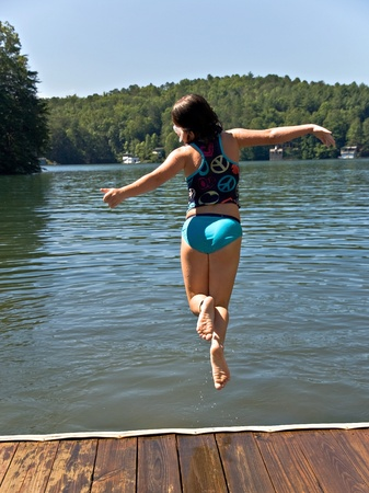 Cute young girl jumping off a dock into a lake. Stock Photo