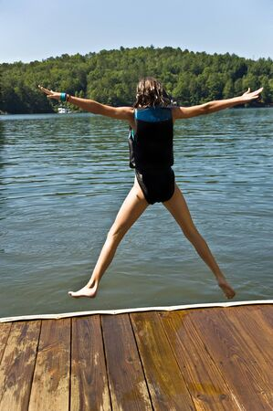 A preteen girl jumping off a dock into a lake. Stock Photo - 9783483