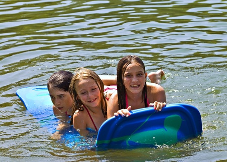 Three cute girls on a float in the water.