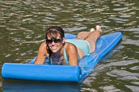 A pretty woman with sunglasses floating in the water. photo