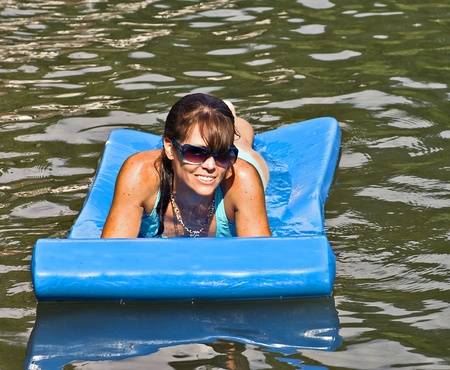 wet girl: A pretty woman on a float in the water happy and smiling.