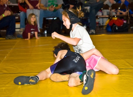 wrestle: ATLANTA, GA USA - DECEMBER 28, 2009:  A young girl and boy wrestling at the Dixie Nationals WrestlingTournament.