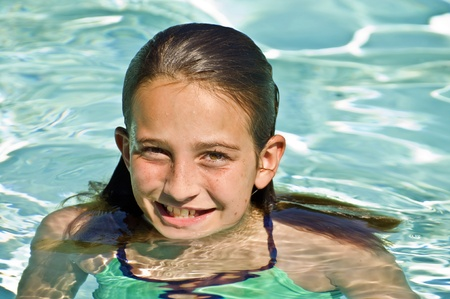 A beautiful smiling preteen girl in a pool.