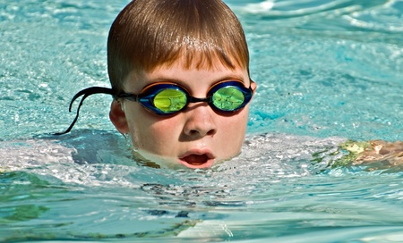 Close up of a preteen boy swimming.  The waves and splashes in the pool are reflected in the goggles.