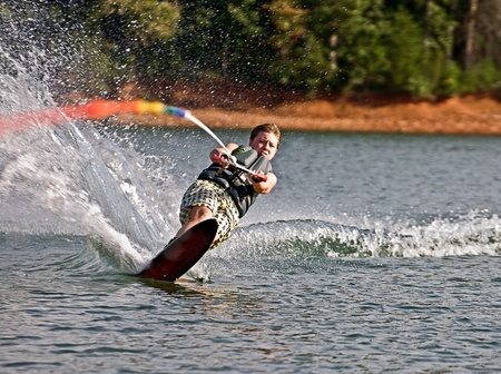 A preteen boy on a slalom ski cutting across the wake with an expression of total concentration.