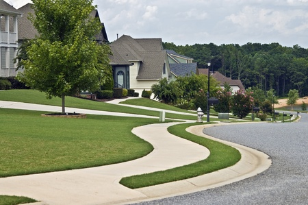 Manicured lawns and curving sidewalks in a modern neighborhood. Stock Photo