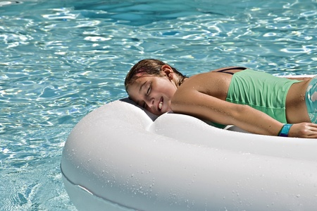 preteen: A preteen girl lying on a large tube sunning in a pool. Stock Photo