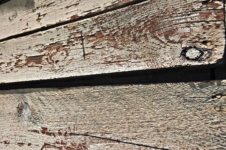 Wood on the side of an old barn, paint peeling and grungy. photo