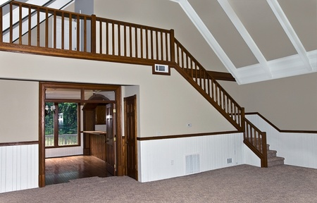 The newly renovated interior of a house showing the carpet, stairway and kitchen entrance. Stock Photo
