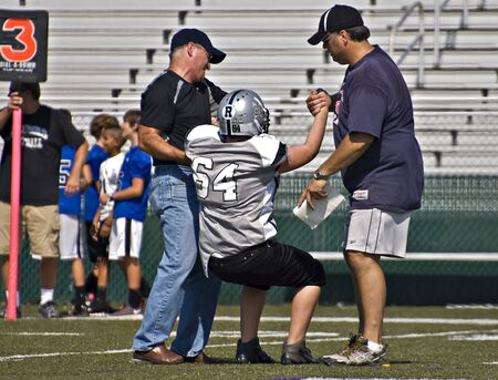 CUMMING, GA, USA - AUGUST 27: Unidentified injured boy helped off the field during a game of 11-13 year-old boys August 27, 2011 in Cumming GA. The Raiders vs The  War Eagles.