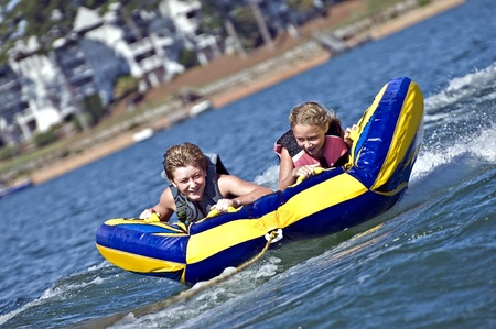 boating: Young boy and girl on a tube behind a boat.