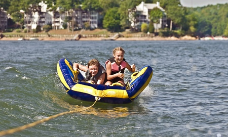 A young boy and girl riding a tube behind a boat. Stock Photo - 10495790