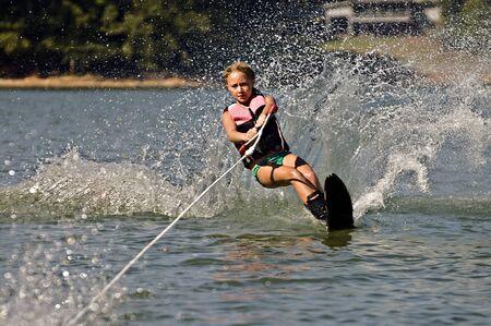 slalom: MÅ'oda dziewczyna na nartach wodnych na kurs slalom. Zdjęcie Seryjne