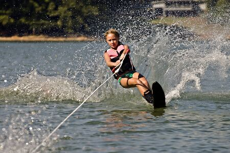 Young girl water skiing on a slalom course.