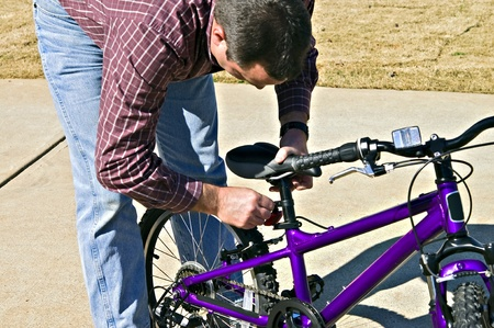 A man fixing the seat of his child's bike.