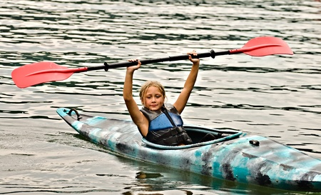 A cute young girl in a kayak holding a paddle above her head giving a signal.