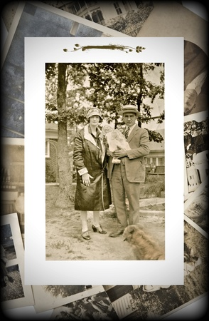 vintage photo: An original vintage photograph of a couple with a baby on a background of old pictures.